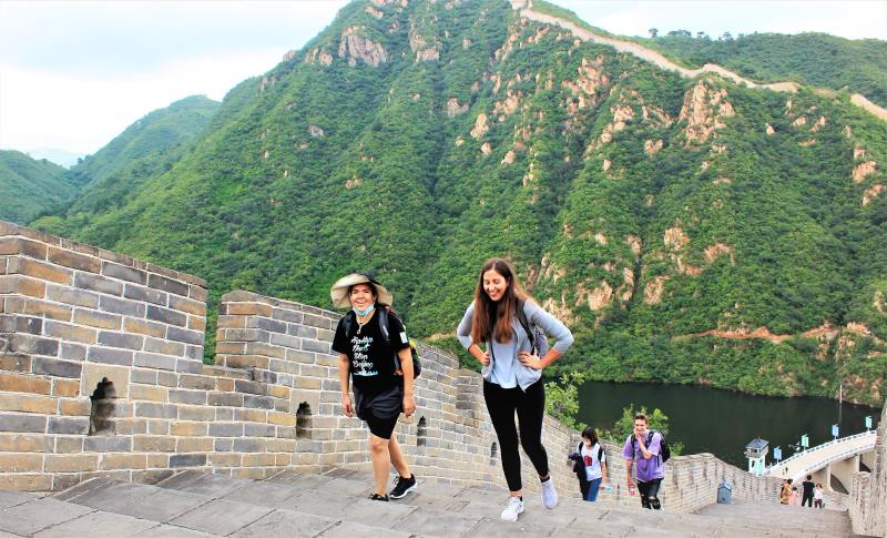 Two members of Female Expats of Beijing (FEB) climbing up lots of steps on the Great Wall of China.